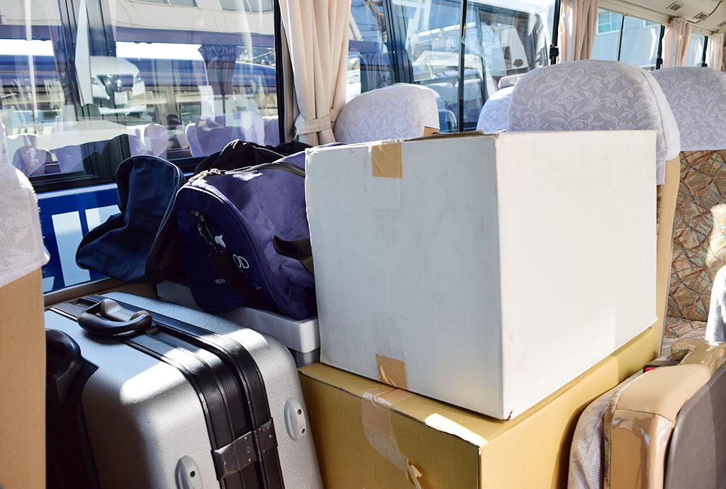 マイクロバスの座席に荷物を載せる